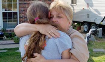 A woman hugs a teenage girl