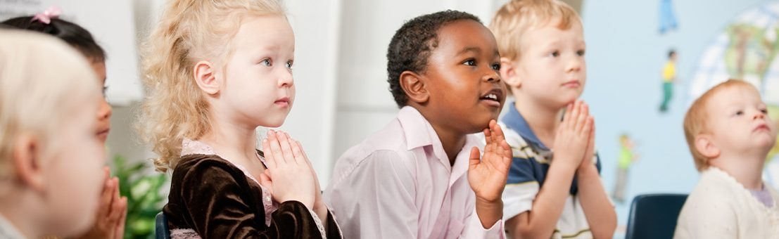 Children with hands in prayer look off camera towards teacher