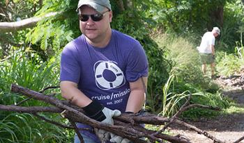 Volunteer carrying sticks and brush