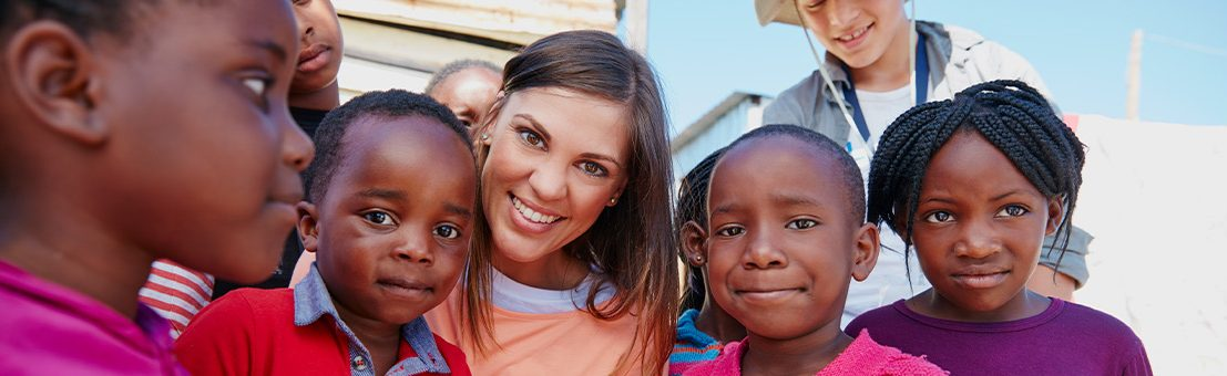 Female volunteer smiles and poses with group of children